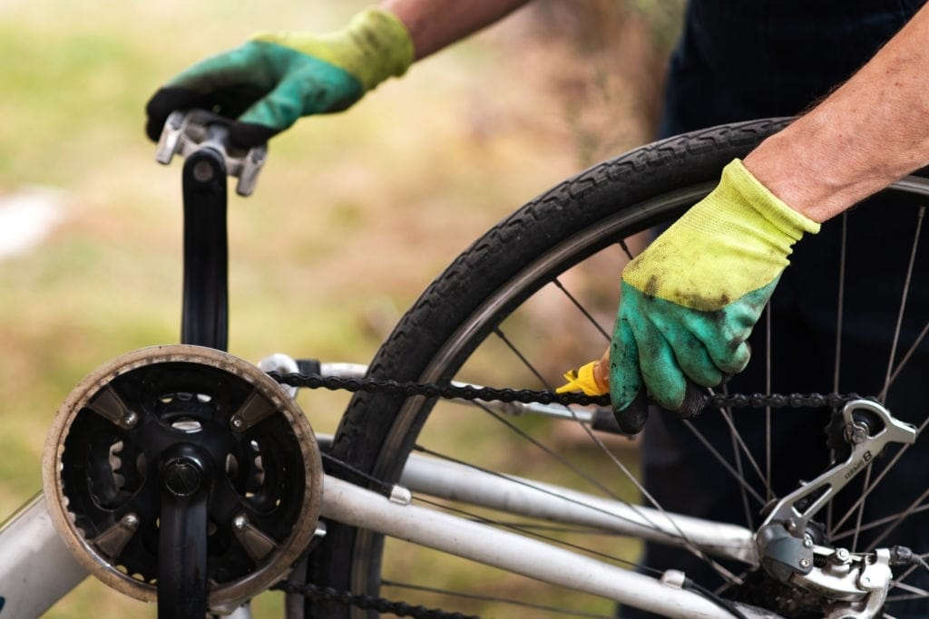 Man lubricating bicycle chain close up